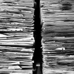 two large stacks of file papers messy