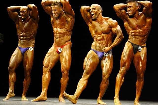 4 body builders on stage in competition
