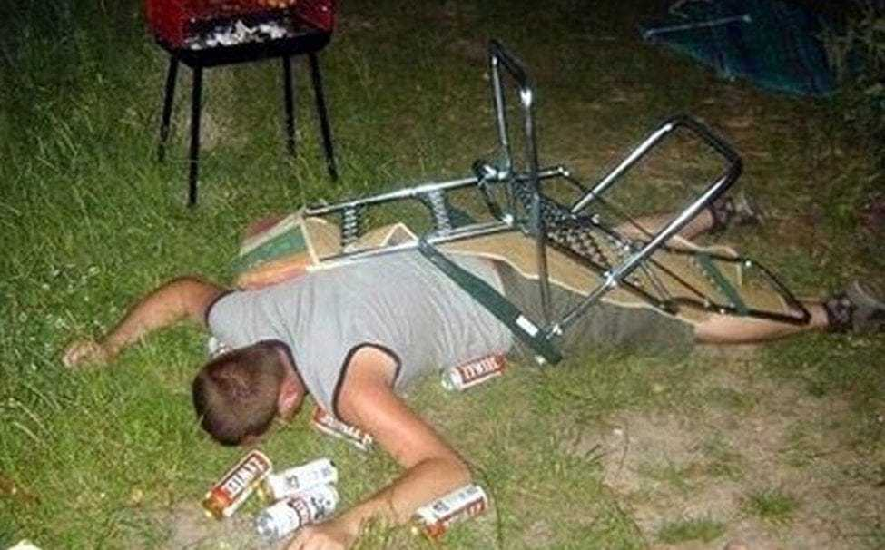 drunk guy face down in lawn with lawn chair on top of him surrounded by beer cans