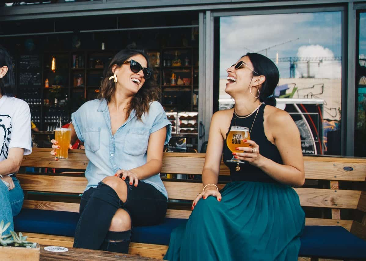 two ladies laughing at outside bar