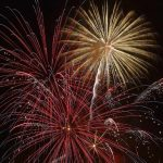 three bursts of fireworks in a dark sky