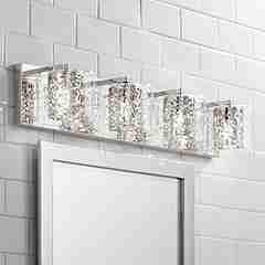 silver light fixture above bathroom mirror
