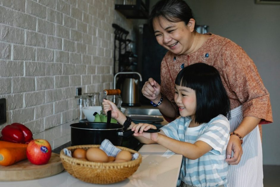 mother daughter cooking in the kitchen and teaching about basic first aid