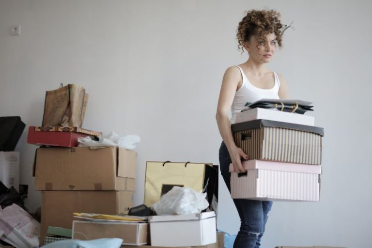 woman carrying boxes to declutter her room