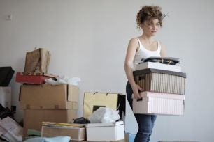 woman carrying boxes declutter house