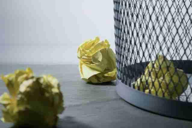 wastebasket with crumpled paper around it