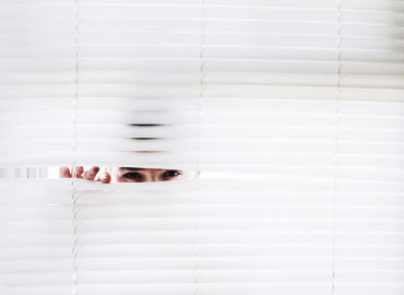 man peeking out of window blinds