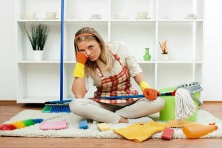 sad woman sitting on floor surrounded by cleaning tools