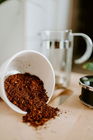 coffee cup filled with coffee grounds spilled on table