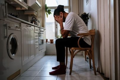 depressed guy kitchen holding head in hands waiting for motivational quotes to help you clean