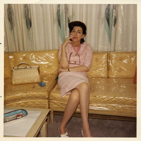 1950s woman sitting on plastic covered couch