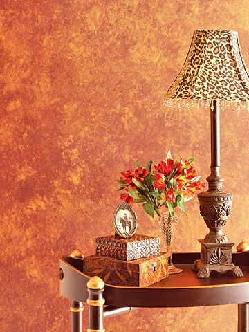 lamp on table in front of peach colored sponge painted walls