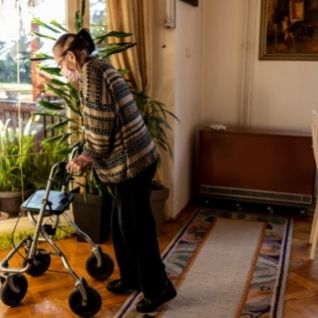 Senior citizen using rollator to clean house
